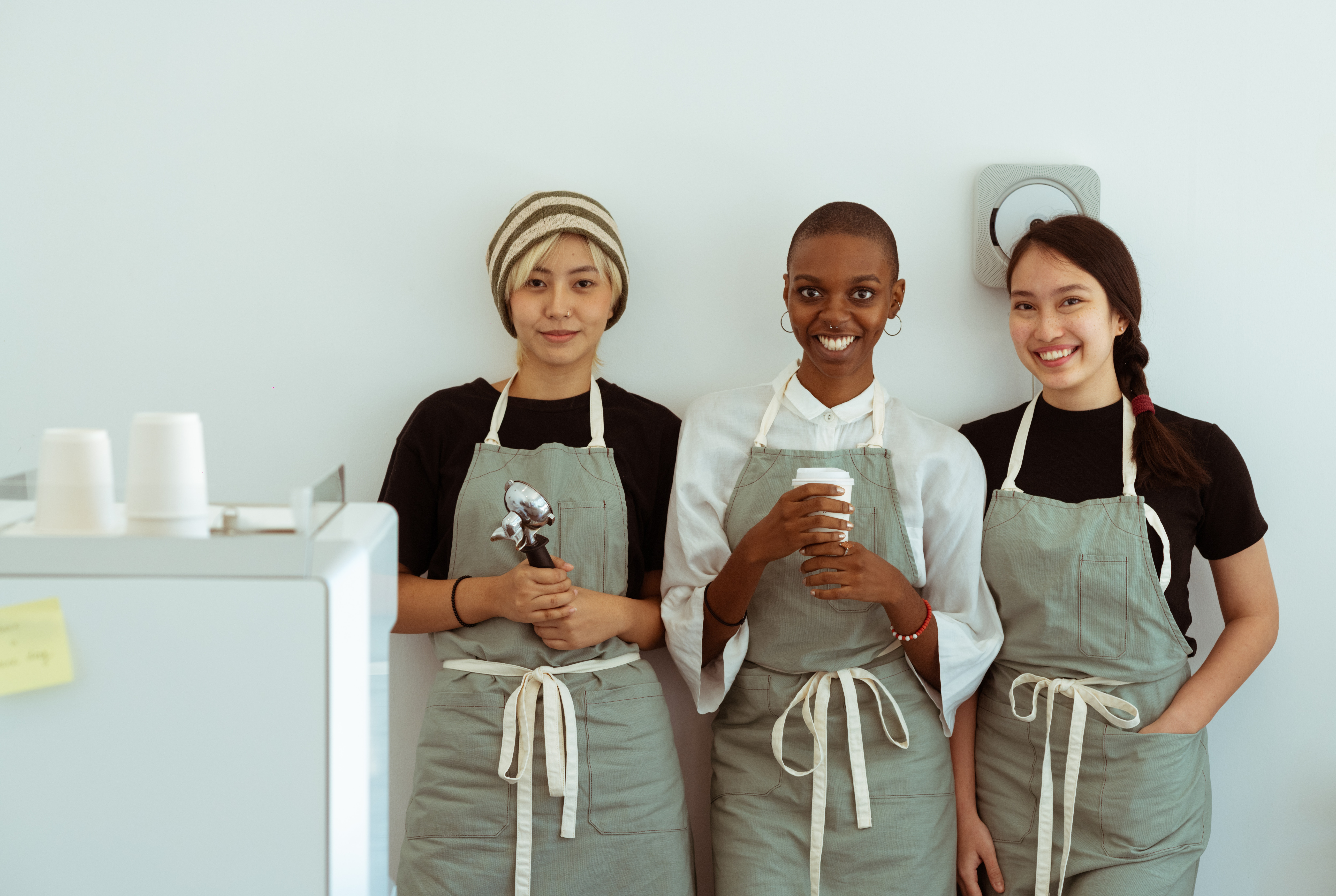 Team of three baristas working in a cafe